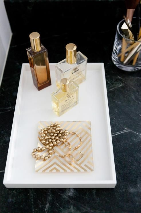 A soapstone vanity top is lined with a white lacquer vanity tray from West Elm lined with gold perfumes and a gold chevron jewelry tray.