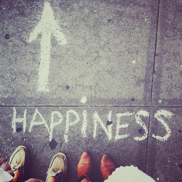 "same perspective, show groom's shoes and bride's dress and instead of ""happiness"" in chalk, write ""happily ever after"" with the arrow pointing ahead."