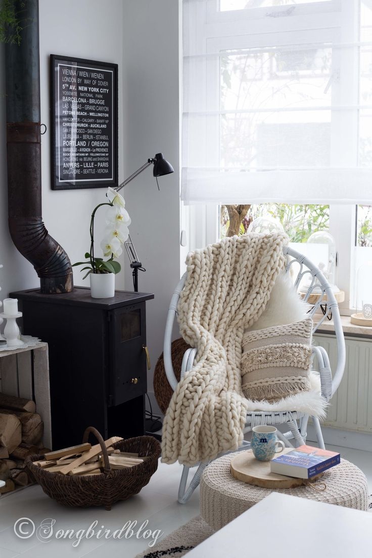 White bohemian living room. Love the white neutral base with the contrast of a black stove. Pillows, throws and a footstool add texture and lots of coziness.