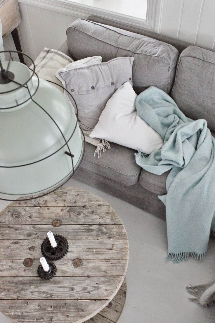 Grey sofa, soft aqua blanket, plaid throw, rustic spool table and vintage light
