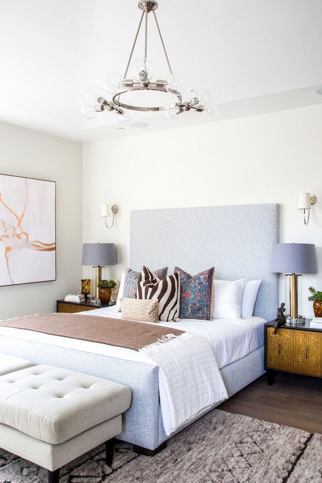 Modern bedroom with a chrome chandelier, a gray linen headboard, and an  animal print
