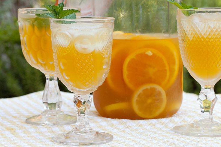 Texas Tea 8 cups water 1-½ cups granulated sugar 2 cups strong tea (3 to 4 regular teabags in 2 cups hot water) 5 lemons, 3 juiced and 2 sliced 2 oranges, 2 juiced and 1 sliced 1 teaspoon vanilla extract 1 teaspoon almond extract Fresh mint