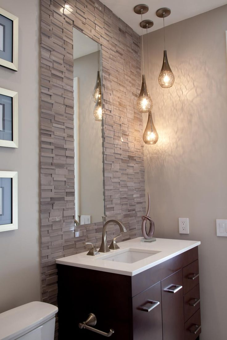 A minimalist vanity with a rectangular undermount sink lends sleek, streamlined style to this transitional-style bathroom. The stacked stone tiles lining the wall add depth to the space, while staggered hanging pendants and a tall, narrow mirror create a brightening, opening effect.