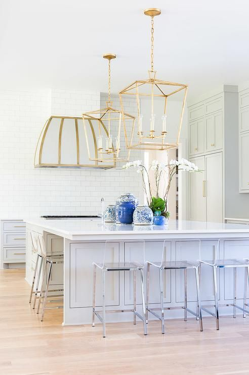 A pair of Darlana 6 Light Lantern illuminating an oversized gray kitchen island topped with a slab of white quartz lined with clear acrylic counter stools, CB2 Vapor Counter Stools.