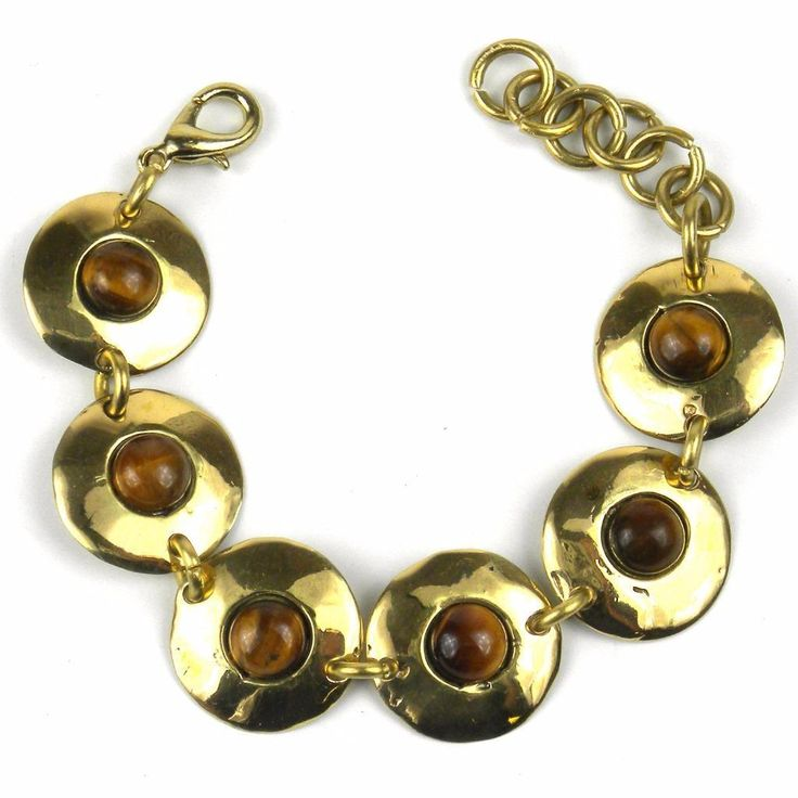 Handcrafted by South African artisans, this link bracelet features six 0.75-inch diameter disks of polished brass each with a tiger's eye center piece. The bracelet, with a lobster-claw closure, is 7 inches long including the 1.5-inch extension chain.
