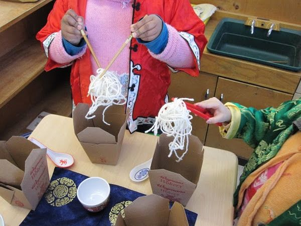Fine motor pretend play- yarn noodles in take out boxes and chopsticks