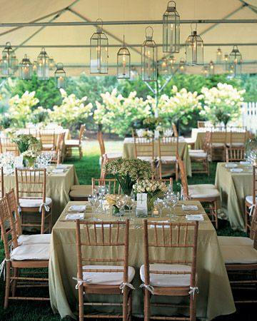 Lanterns cast a warm glow under a tent at this backyard wedding