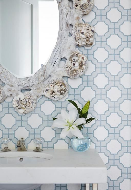 Beautifully styled white and blue cottage powder room is clad in Phillip Jeffries Imperial Gates Wallpaper and boasts an eye-catching oval whitewashed ...