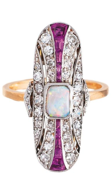 An Art-Déco opal diamond ring with ruby setting C. 1920. 18 ct. yellow gold, platinized. Long ringtop with one central opal (5,5 x 4 mm) and on the sides 10 rubies in baguette and trapez cut.