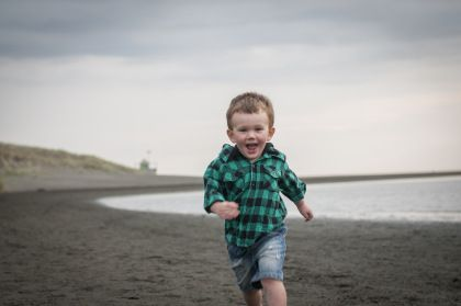 Happy running, Bethells beach, little boy photoshoot by Anais Photography, Auckland
