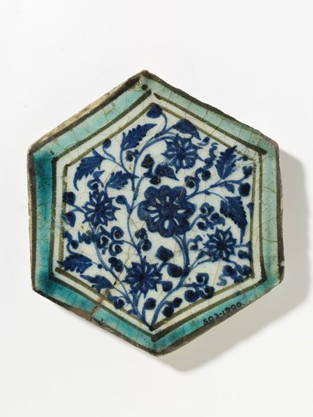 Tile | Made in Damascus, Syria, 1400-1450 | Materials: fritware, painted in underglaze cobalt blue and turquoise | Tile, fritware, hexagonal, painted in underglaze blue with flowers and leaves on wavy stems, within a turquoise border outlined in manganese-black | VA Museum, London