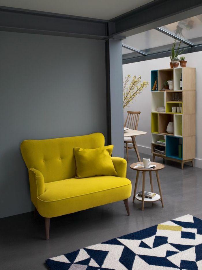 un joli canapé jaune pour le salon avec un tapis blanc et noir murs gris