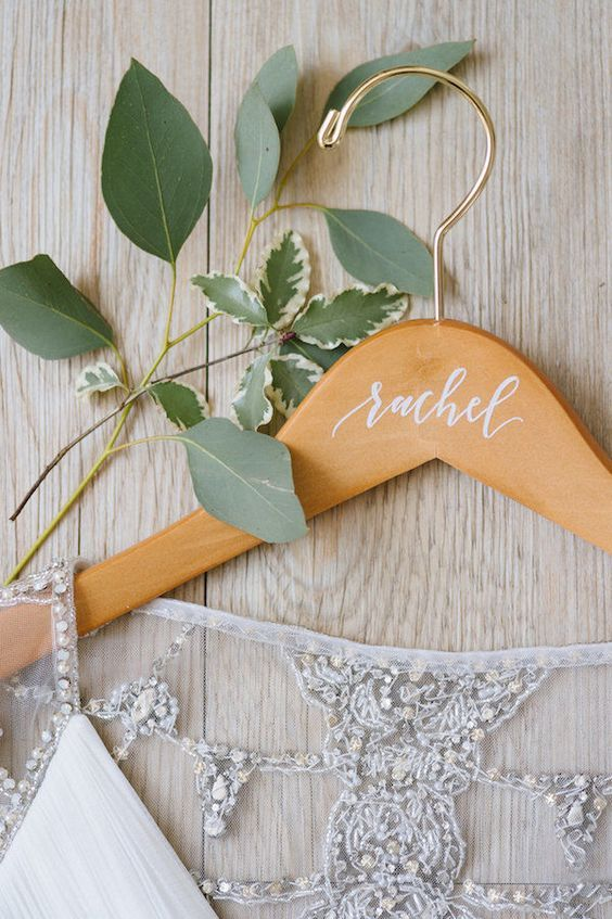 DIY Wedding Ideas for Brides Who Love Lettering | Custom hangers are the perfect gift to give to your bridal squad to thank them for being a part of your special day. Find wooden hangers and write each of your bridesmaid's names in white, black or gold beneath the hook. Plus, they look great for pictures and it's a gift they'll be able to treasure forever.
