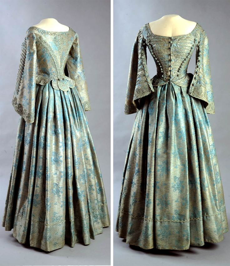 Dress, Hungary, ca. 1860. Silk, two pieces. Turquoise material decorated with small black lines & scattered turquoise rose boughs & leaves. Attenuated, boned bodice. Cords & buttons knit of turquoise & white cotton yarn. Chest is richly corded & closes with braided buttons in front. Waist lobe frills enriched with cord tulip stems. Draped, loose skirt lined by woven braids on bottom. Museum of Applied Arts, Budapest