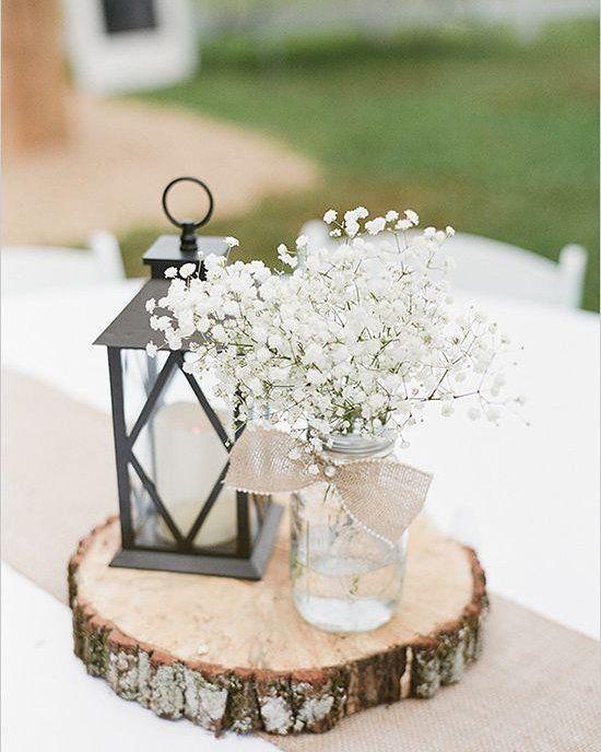 Um combinação de potinho com flores pedaços de tronco de madeira e velas pode ser a decoração perfeita para a mesa dos convidados!