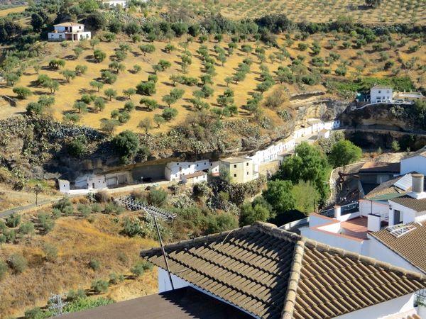 Ook Setenil de las Bodegas ligt op de route van de pueblos blancos in Andalusië, aan de rand van de prachtige provincie Cadiz. Een middeleeuwse toren steekt hoog boven het plaatsje uit. Op het eerste gezicht lijken de huizen bijna te verdwijnen onder het gewicht van een enorme overhellende rots. Maar de uitgesleten kloof van de rivier Rio Trejo blijkt voor veel mensen toch al eeuwenlang een ideale woonruimte, waar het zowel 's zomers als ook in de winter heerlijk vertoeven is.