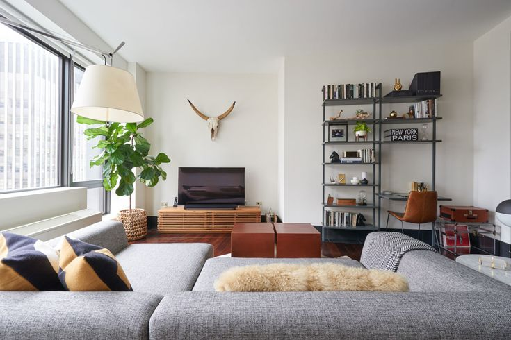 """Since the couple is from California but live in New York, they wanted to mix a laid-back California vibe with Manhattan luxe. The living room, with its decidedly southwestern <a href=""""https://www.restorationhardware.com/catalog/product/product.jsp?productId=prod70010&categoryId=cat160004"""" target=""""_blank"""">horns</a> and <a href=""""http://www.cb2.com/cowhide-rug-5x8/s476632"""" target=""""_blank"""">cowhide rug</a>, balanced by the modern <a href=""""http://www.cb2.com/uno-2-piece-sectional-sofa/s372042""""…"""