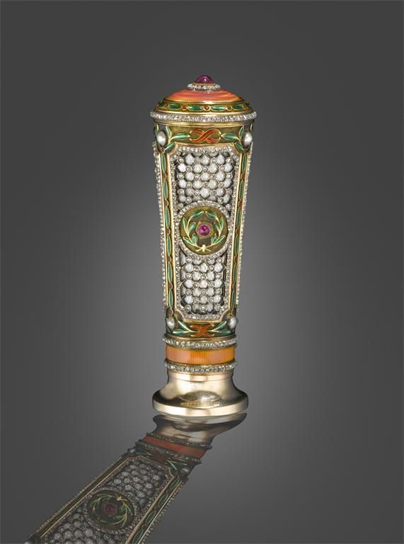 A Fabergé parasol handle in the Louis XVI manner. Workmaster Michael Perchin. Of tapered cylindrical form with three trellis panels set with diamonds on oyster coloured enamel ground, with cabochon rubies in green enamel laurels and further diamond borders. The panels separated with green and red enamel foliate lines and pearls. The top with a cabochon ruby within diamond border on a pink guilloche enamel ground. The base with a band of similar coloured enamel between diamond bands.
