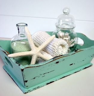 Great for a beach house guest room or bathroom decor. Details matter. Wood tray, starfish, shells in apothecary jar, seafoam.