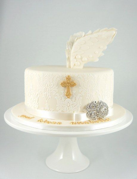 Angel Cake ivory coloured with royal icing stencilling topped with fondant 3 d angel wings. Christening, birthday, wedding cake.