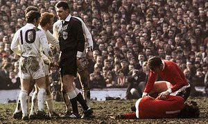 Referee Jack Taylor talks to Leeds United's Billy Bremner as Manchester United's Pat Crerand
