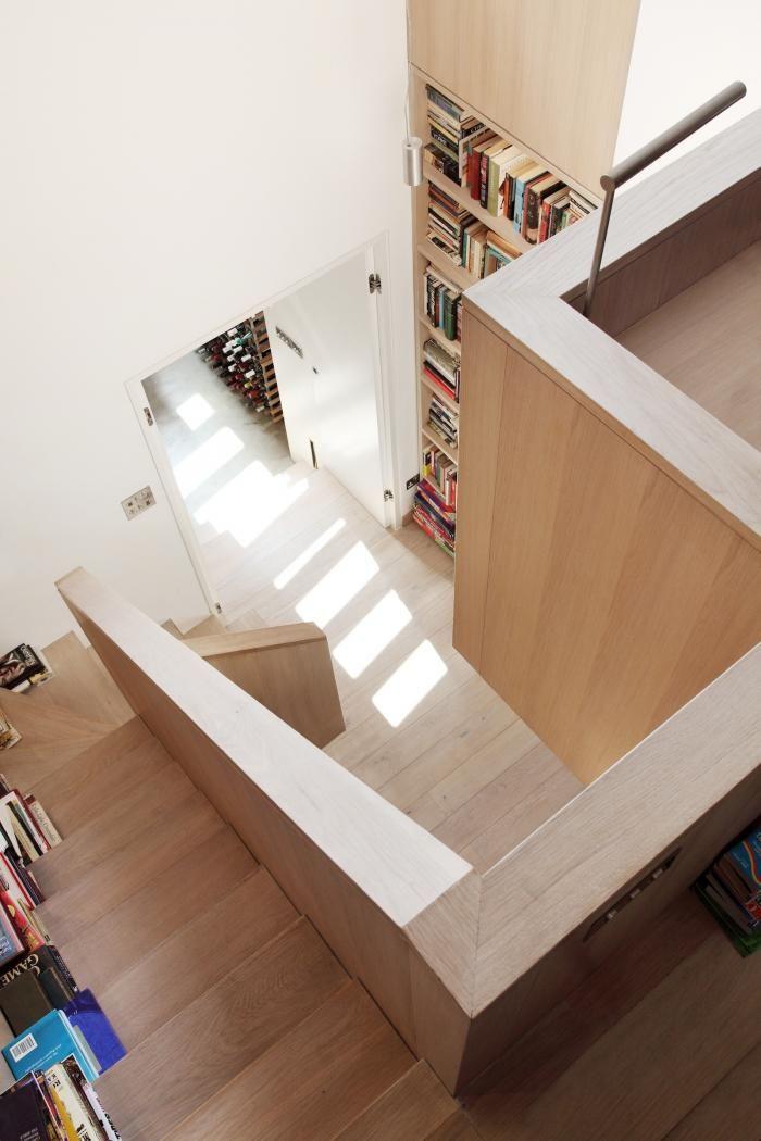 Oak staircase in London townhouse full height bookshelf wall