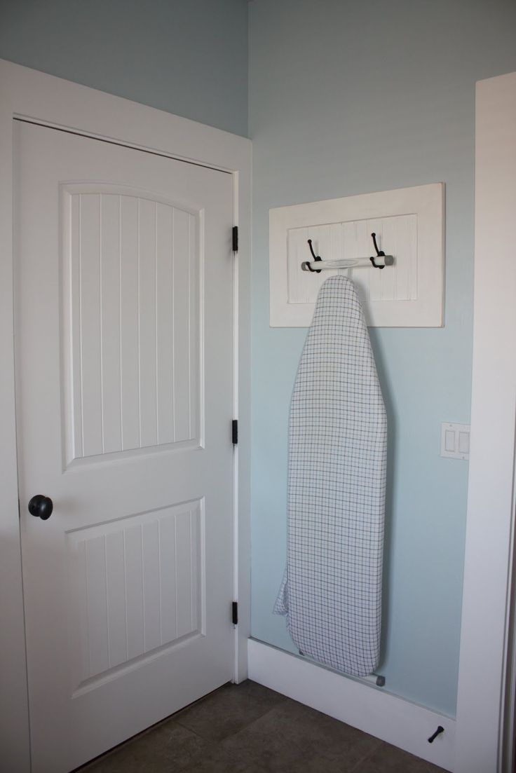 Use 2 coat hooks to hang an ironing board.