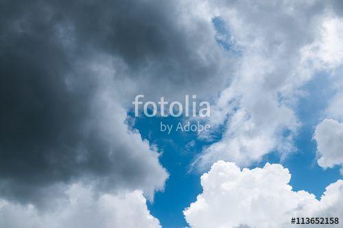 Aufziehendes Gewitter, dramatischer Wolkenhimmel mit hohen weißen Cumulus-Wolken und dunkelgrauen Gewitterwolken vor noch blauem Sommerhimmel, Quellwolken