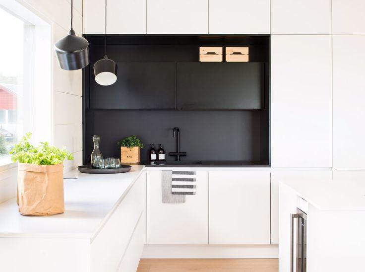 Sisustussuunnittelija Anna Tuohimaan ehdotuksesta valkoiseen keittiöön tehtiin musta syvennys, Lube. Musta hana, Tapwell. Pasila-riippuvalaisimet, Innolux.