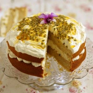 Egg free cake on a cake stand covered in cream and passion fruit and topped with a purple flower.