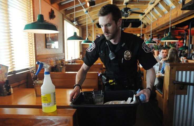 Iowa State University Police Officer Anthony Greiter cleans tables during a free lunch fundraising event for Special Olympics at Texas Roadhouse restaurant on Thursday in Ames. Photo by Nirmalendu Majumdar/Ames Tribune http://www.amestrib.com/news/20170413/officers-become-waiters-to-support-special-olympics