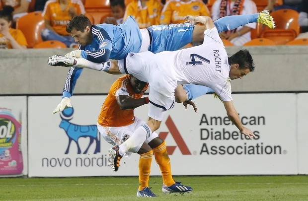 Dynamo keeper Tally Hall, in blue, makes a save in front Vancouver Whitecaps Alain Rochat March 23.