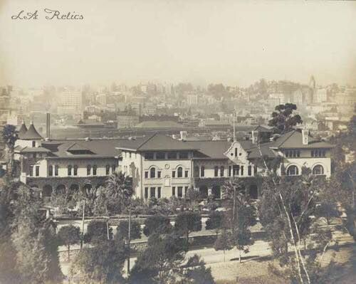 Aerial of Hollenbeck Home for the Aged, located at 573 South Boyle Avenue. Dedicated September 1896, expanded to include library, hospital and other buildings. Spanish Colonial Revival style architecture with cupolas, tile roof, cloisters, domed chapel and gardens of exotic and tropical plants; Morgan, Walls & Morgan, architects. Photo dated between 1914 & 1923. Source: California State Library