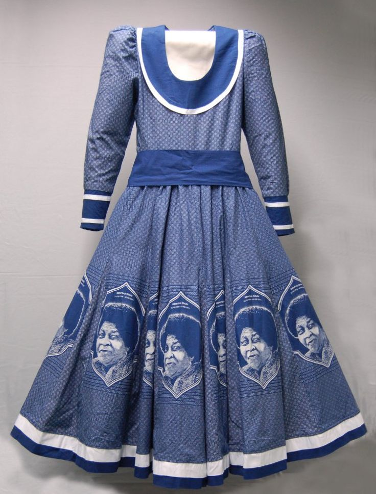 A tailored woman's dress with open neck, long sleeves, sash/belt and flared skirt made out of indigo dyed discharge printed fabric manufactured by Da Gama Textiles and known as 'Shweshwe'. Additional panels across the skirt bear the image of Albertina Sisulu with the dates