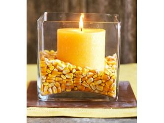 The corn in the vase could be swapped out for sunflower seeds, small pebbles, or coffee beans. The candle color could coordinate with the wedding colors, or a bloom could be added for a floral touch.