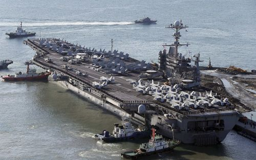 """The nuclear-powered aircraft supercarrier USS George Washington is escorted into a navy port in Busan, South Korea, Friday, Oct. 4, 2013. The U.S. carrier is in South Korea to join the ongoing South Korea and U.S. joint military drill. On Tuesday, Oct. 8, North Korea warned the United States of a """"horrible disaster"""" and put its troops on alert over the naval drill involving the carrier alongside South Korean and Japanese vessels. (AP Photo/Yonhap, Jo Jung-ho)"""