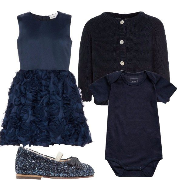 Outfit composto da vestito blu con delle applicazioni sulla gonna che formano delle rose, cardigan blu, body blu e ballerine glitterate con cinturino.