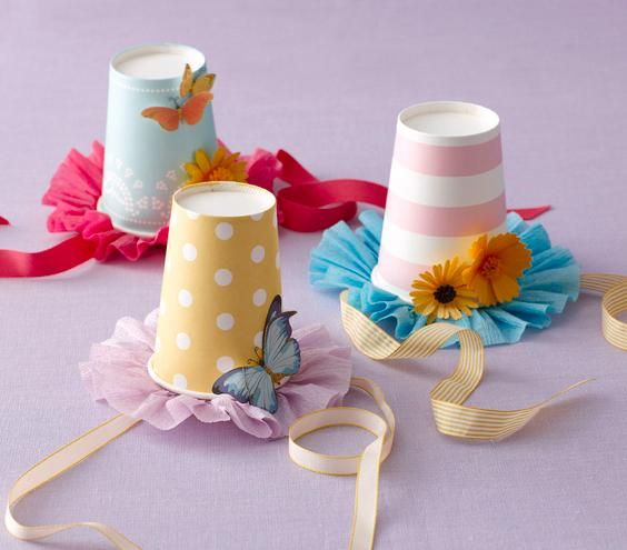 DIY Party Hats: Start with paper cups, poke holes on the side for stringing ribbon through, and adorn with stickers and embellishments.