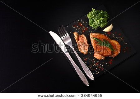 Juicy roast duck breast on a black table and cutlery