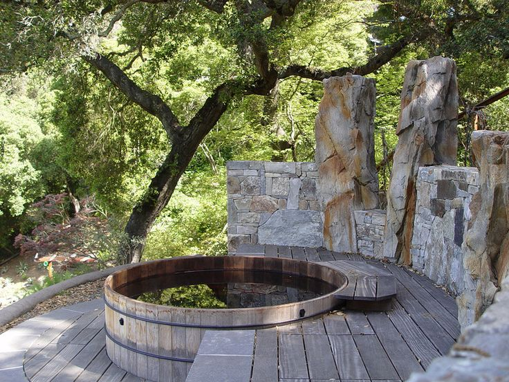 Wood and stone. A stone wall makes a striking backdrop to this redwood hot tub tucked among the trees. The tall stone pillars also help block wind and provide privacy.