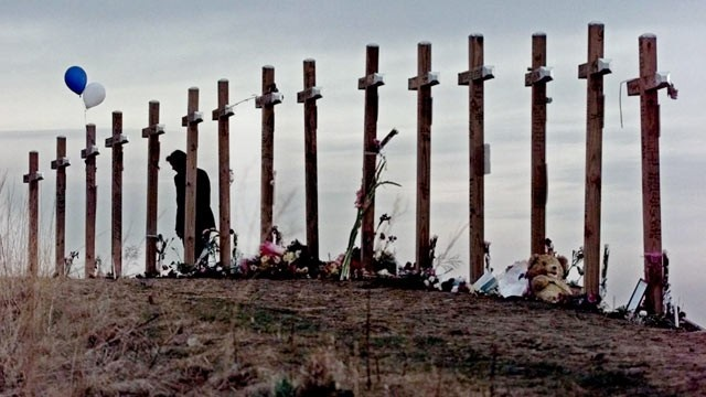 PHOTO: This April 28, 1999 file photo shows an unidentified woman with 15 crosses posted on a hill above Columbine High School in Littleton, Colo. on April 28, 1999 in remembrance of the 15 people who died during a school shooting on April 20.