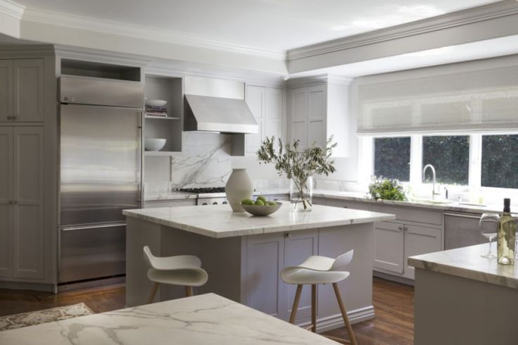 """In Mead Quin's latest Atherton project, the kitchen was reinvented with a palette of gray and white. """"They were thinking of starting over completely, but when we considered how well the existing cabinets were made, we decided to give paint a chance,"""" says Quin. Marble counters replaced the old granite, and Quin chose all new hardware, fixturesThe kitchen window coverings are Conrad, fabricated by Riitta Herwitz. and barstools by Anyon and art is from Dolby Chadwick. Photo: David Duncan ..."""