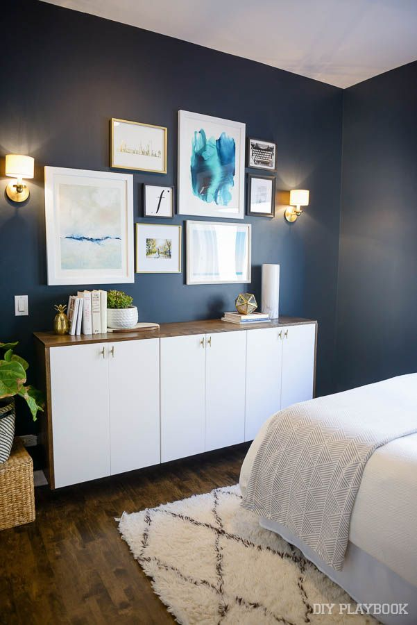 Love a big gallery wall over a dresser or credenza. These frames look amazing on the dark navy painted wall in this bedroom.