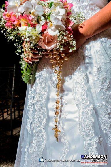 Terço confeccionado com pérolas cremes em abs 12m/m, banho em (ouro) dourado,Medalha de Nossa Senhora Aparecida com strass,Crucifixo,entremeio Aparecida resinado em preto e branco,rondelas em metal dourado com pedras imitação em cristal.    Como usar o terço de noiva:  - O terço pode ser enrolado no punho da noiva, deixando cerca de 10 cm soltos, quando o terço e o bouquet forem pequenos;  - Pode ser colocado sobre as flores do bouquet;  - Envolvido no caule das flores que compõem o bouquet…