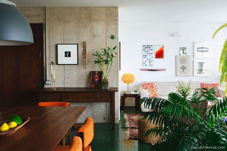 Integração de sala de estar e sala de jantar. O piso de hidráulico verde e o concreto são destaques no apê.