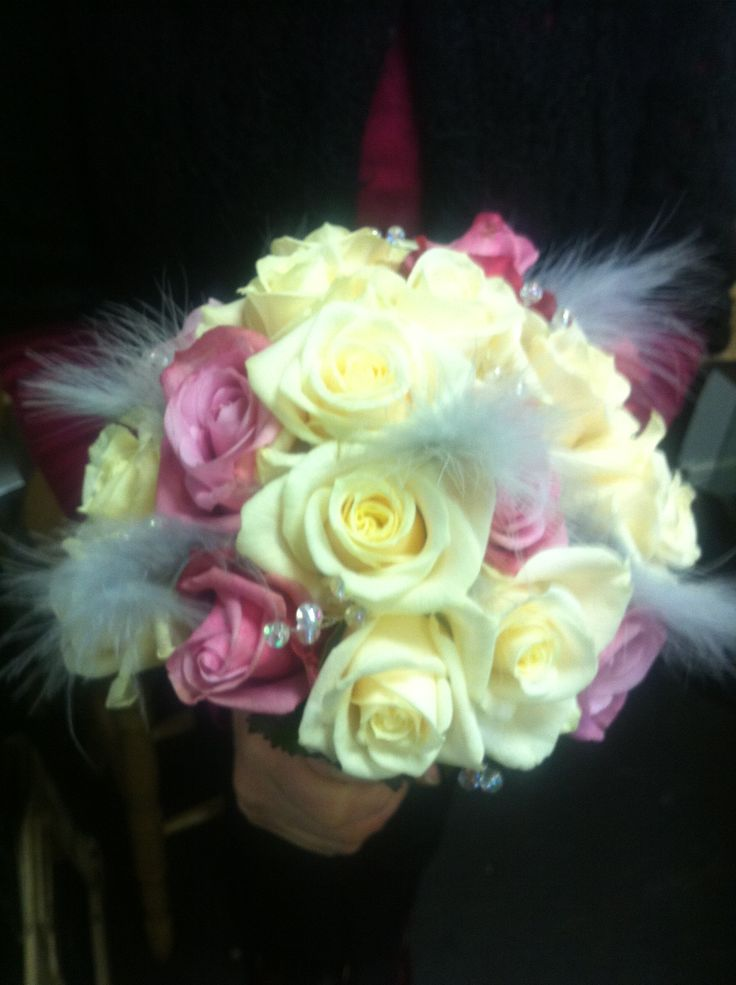 A mixed rose bouquet with feathers and silver berries.