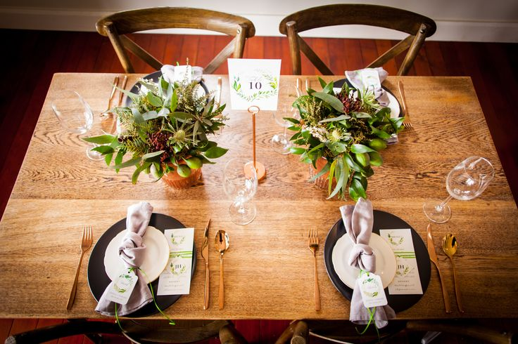 Green and White Wedding Inspiration. Simple stylish tables with copper cutlery, matte black plates and linen napkins. Flowers and Styling by One Poppy wedding flowers Auckland. Tableware by the Pretty Prop Shop, Stationery by Inspired Weddings, Photography by The Unmissable.