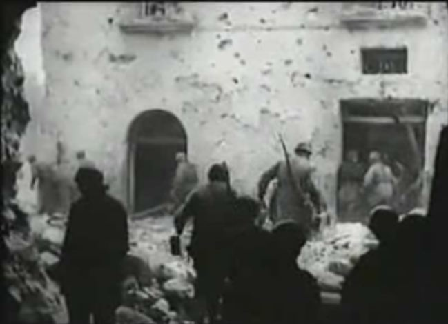 Fallschirmjägern advance from the large opening (of five total openings) on the north end of Palazzo Iucci towards Palazzo Sivlestri. Leutnant Renisch (Kommandeur Of II./Fallschirmjäger-Regiment 1) is standing in the left front of the frame. This frame is from a german newsreel (Die Deutschen Wochenschau Nr. 709)