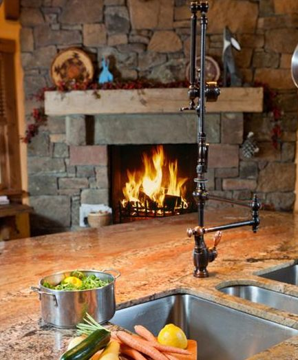 rustic rock fireplace on the edge of the kitchen...and check out that kitchen faucet...major lust!
