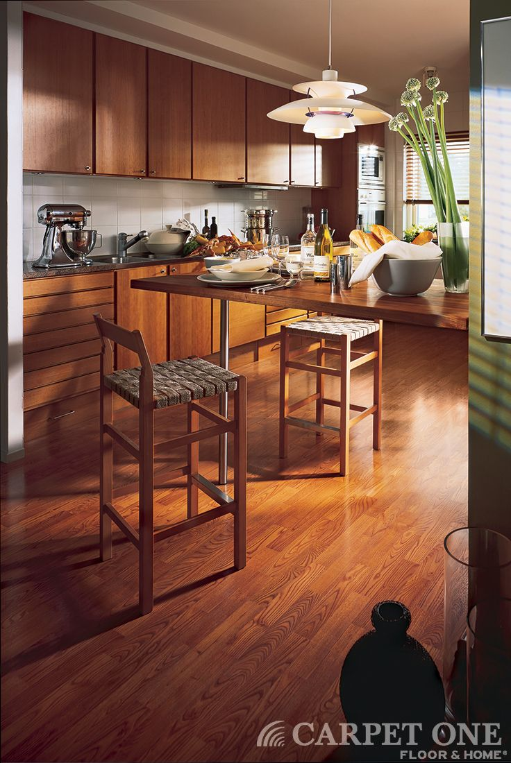 Laminate floors from Carpet One are the perfect choice for those rooms in your home that get a lot of traffic. This kitchen has the beautiful look of natural hardwood floor.  Find more inspiration on our blog BeautifulDesignMadeSimple.com #homedecor #floors.